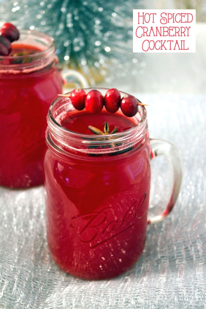 A mason jar filled with hot spiced cranberry cocktail with star anise and cranberry garnish with a second cocktail and tinsel in the background with recipe title at top