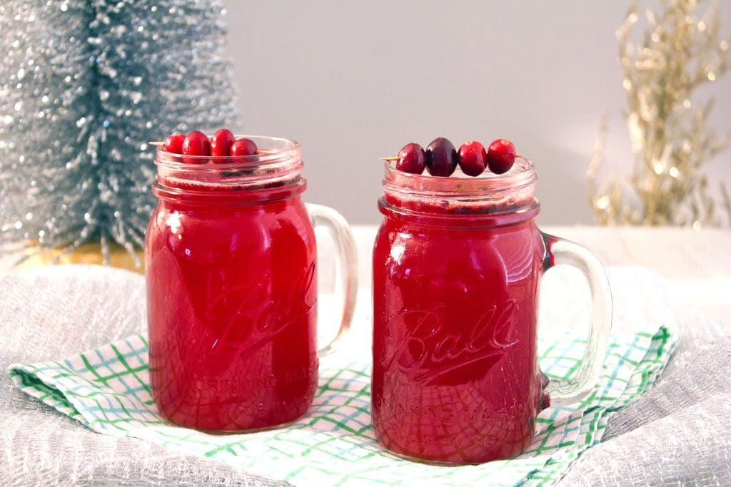 A landscape photo featuring two mason jars of hot spiced cranberry cocktails with cranberry garnishes and a small tinsel tree in the background
