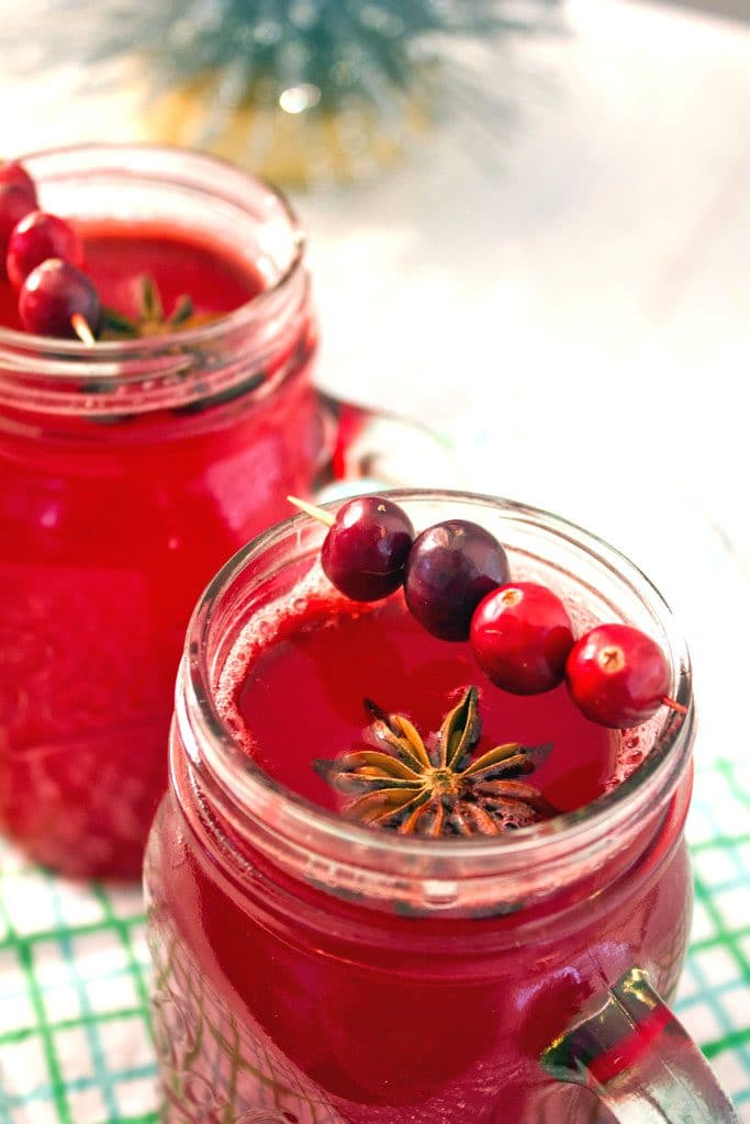 Overhead view featuring the top of a mason jar filled with hot spiced cranberry cocktail with star anise and cranberry garnish and a second cocktail in the background