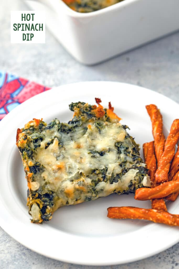 Serving of hot spinach dip on a white plate with mini pretzels on the side and recipe title at top