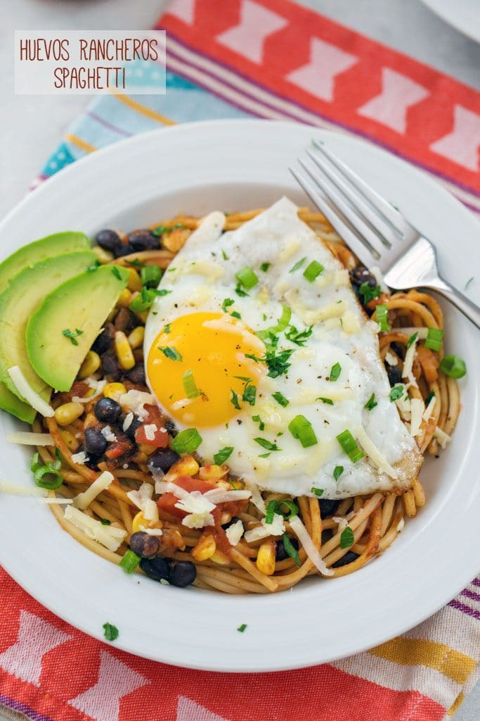 "From-above view of huevos rancheros spaghetti with a fried egg, sliced avocado, black beans, corn, cheese, and cilantro with ""Huevos Rancheros Spaghetti"" text at top"