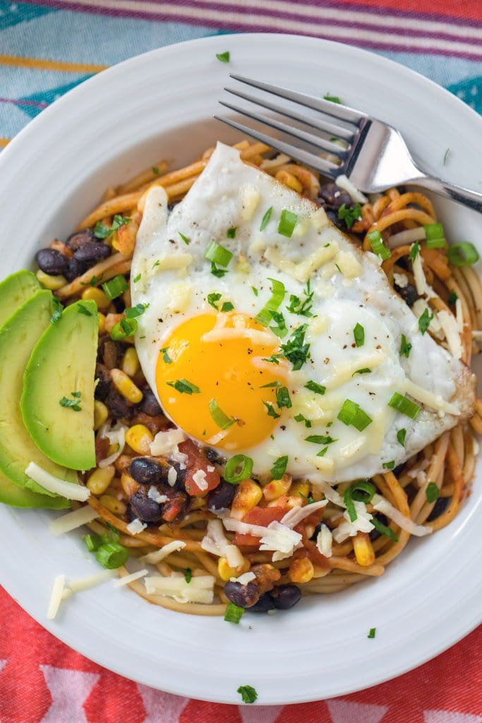 Bird's eye view of huevo rancheros spaghetti on a white plate topped with fried egg, sliced avocado, black beans, corn, cheese, and cilantro