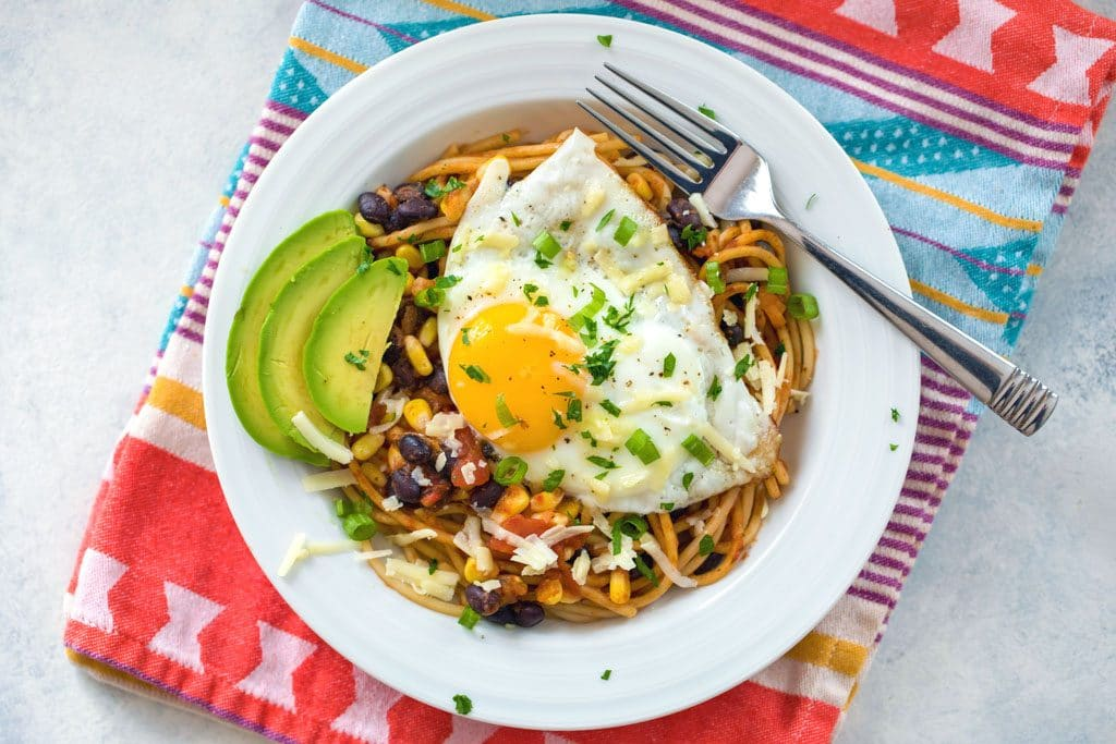Landscape view of huevos rancheros spaghetti on a white plate and colorful napkin with fried egg, sliced avocado, black beans, corn, cheese, salsa, and cilantro and a fork