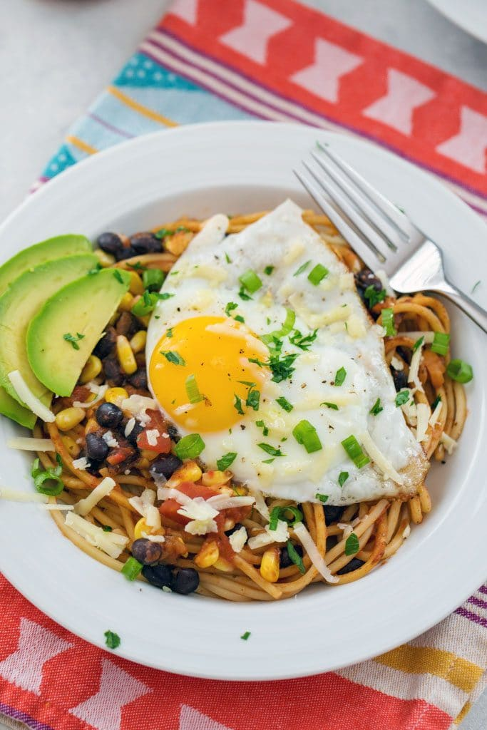 From-above view of huevos rancheros spaghetti with a fried egg, sliced avocado, black beans, corn, salsa, cheese, and cilantro