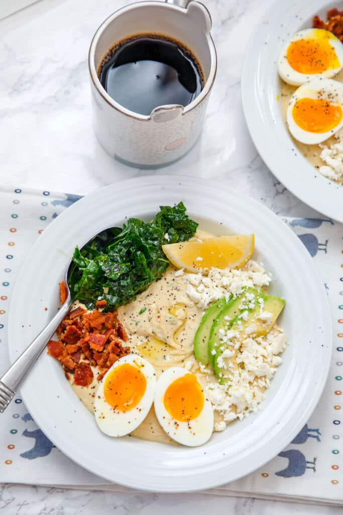 Overhead view of hummus breakfast bowl with halved soft-boiled egg, crumbled bacon, feta cheese, sliced avocado, kale, and lemon wedge with cup of coffee and second hummus bowl in the background