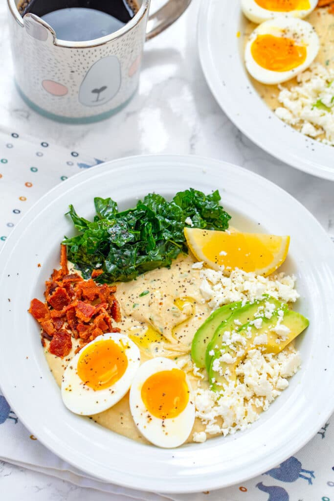 Overhead closeup view of hummus breakfast bowl with halved soft-boiled egg, crumbled bacon, feta cheese, sliced avocado, kale, and lemon wedge with cup of coffee and second hummus bowl in the background
