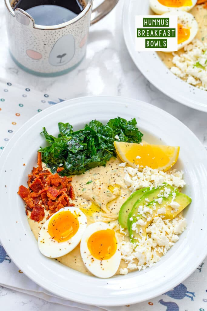 Overhead closeup view of hummus breakfast bowl with halved soft-boiled egg, crumbled bacon, feta cheese, sliced avocado, kale, and lemon wedge with cup of coffee and second hummus bowl in the background with recipe title at top