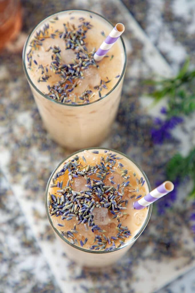 Overhead view of two glasses of iced lavender latte with lavender buds on top and purple and white straws