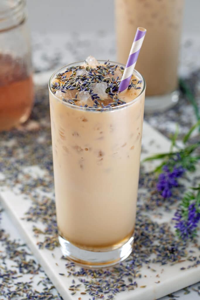 View of a tall glass of an iced lavender latte with lavender buds sprinkled on top and all around and jar of lavender simple syrup in background
