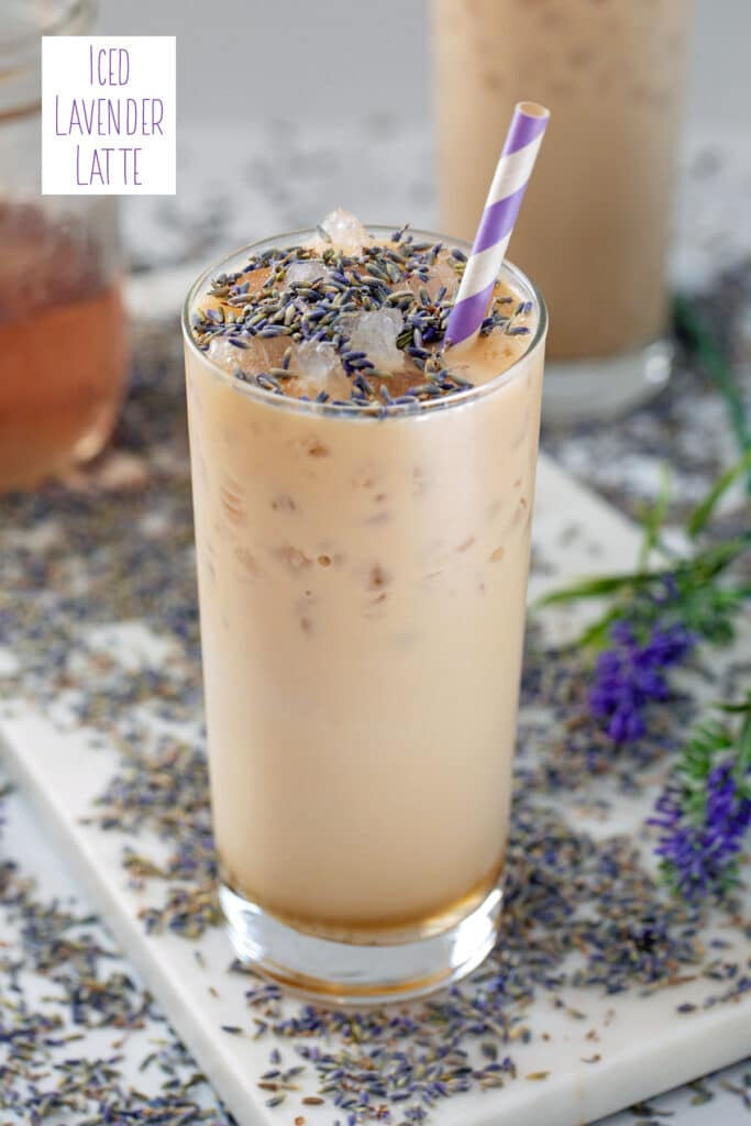 View of a tall glass of an iced lavender latte with lavender buds sprinkled on top and all around and jar of lavender simple syrup in background with recipe title at top