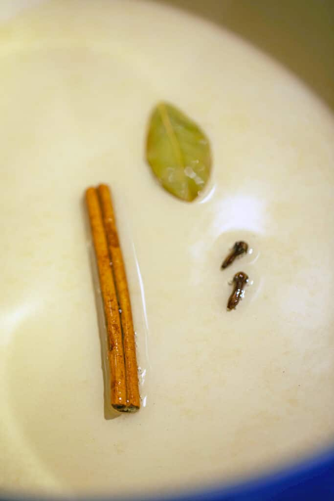 Cinnamon stick, bay leaf, and cloves in olive oil in dutch oven