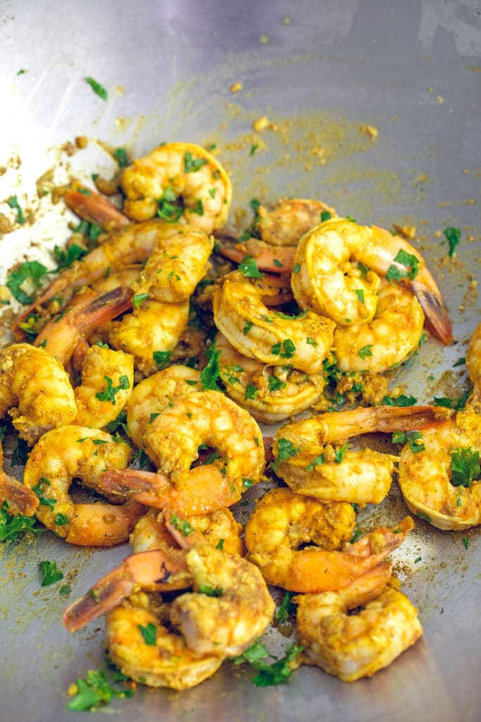 Shrimp cooking in a wok with cilantro