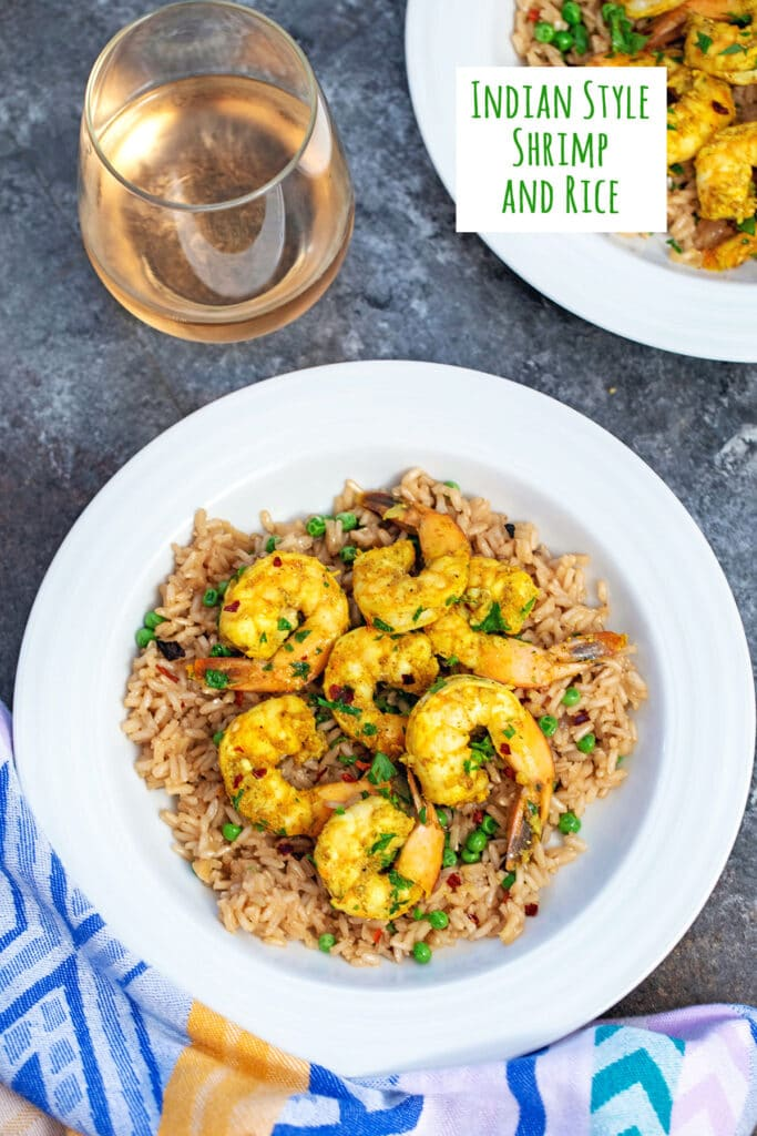 Overhead view of a bowl of Indian style shrimp over brown rice with peas with a second bowl in background and a glass of wine with recipe title at top