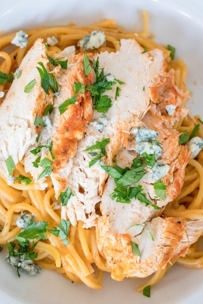 Overhead close-up view of buffalo chicken over pasta with parsley and blue cheese made in Instant Pot