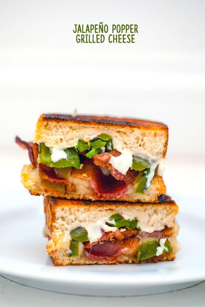 "Head-on view of two halves of a jalapeño popper grilled cheese sandwich stacked on top of each other on a white plate with ""Jalapeño Popper Grilled Cheese"" text at top"