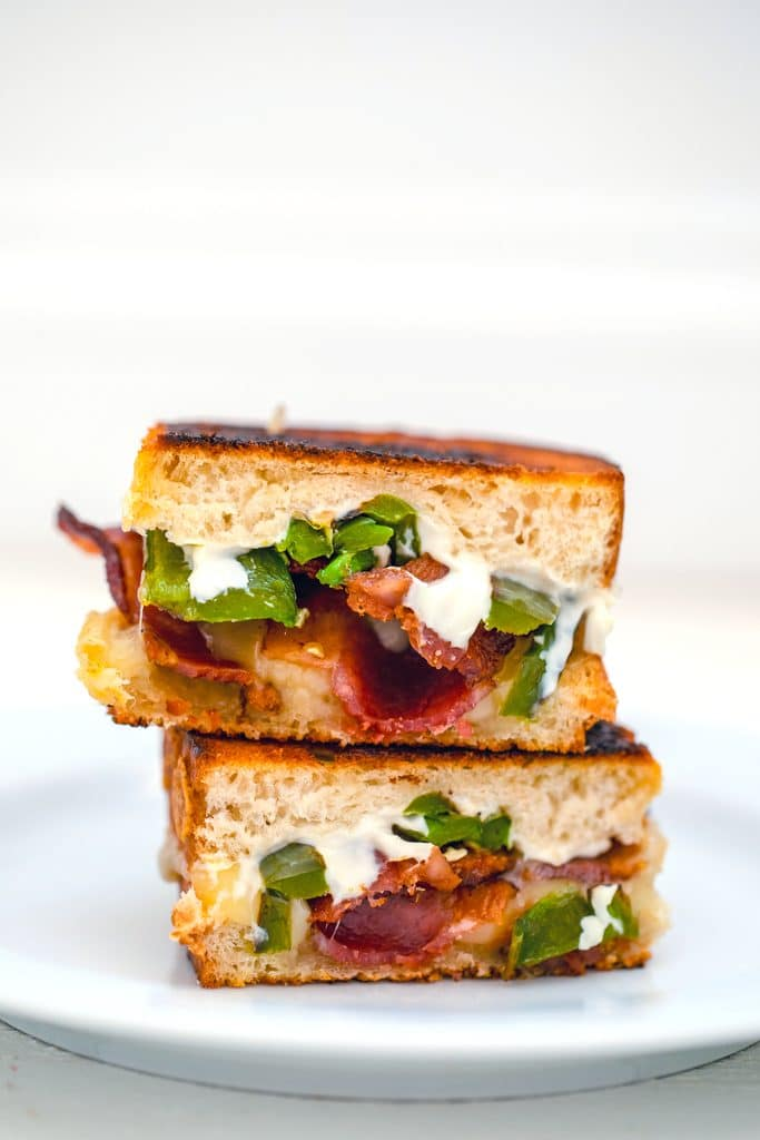 Head-on view of two halves of a jalapeño popper grilled cheese sandwich stacked on top of each other on a white plate