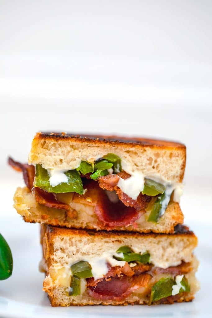 Close-up head-on photo of two jalapeño popper grilled cheese sandwich halves stacked on top of each other on a white plate