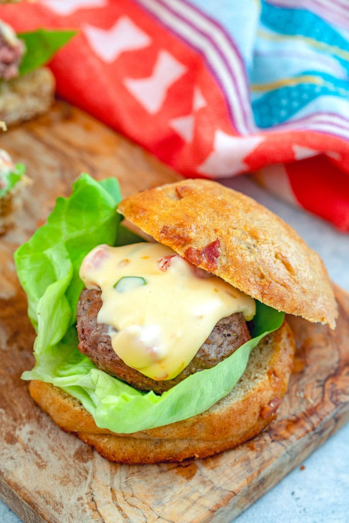 Overhead closeup view of a jalapeño burger with lots of queso on a bacon roll with a leaf of lettuce on a wooden cutting board
