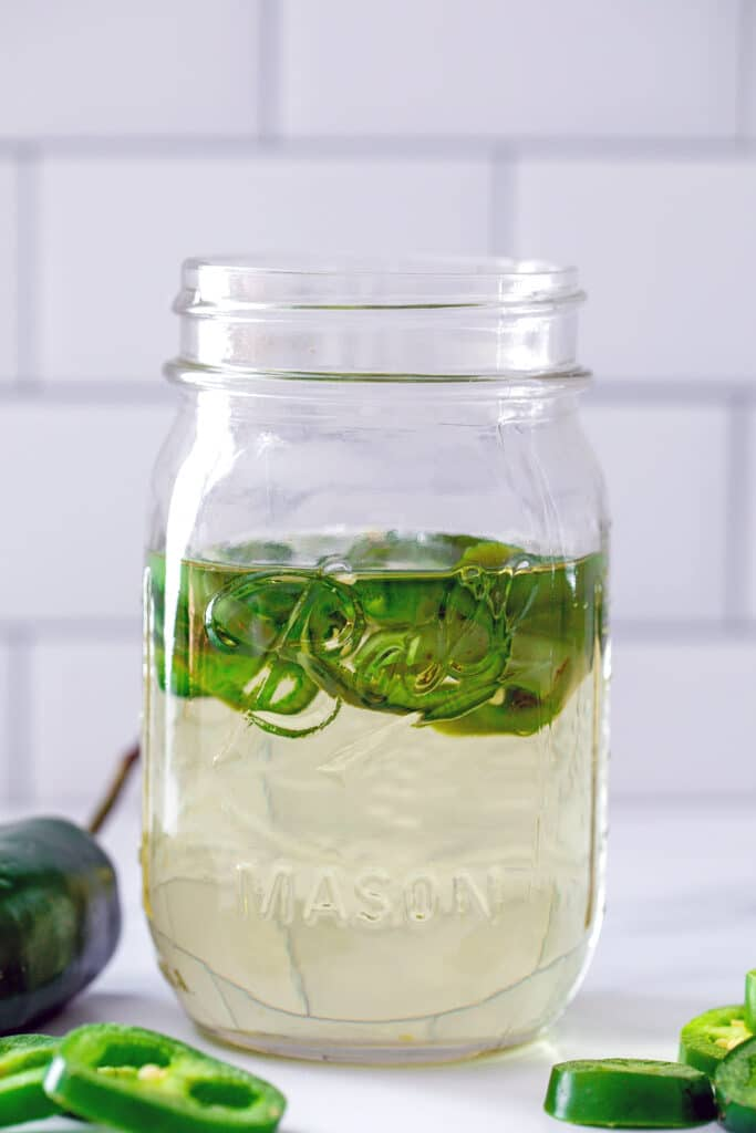 Head-on view of a mason jar filled with jalapeño simple syrup with sliced jalapeños in it and on the table in front
