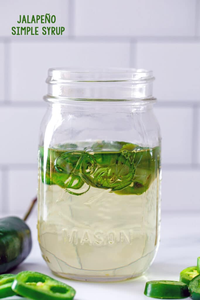 Head-on view of a mason jar filled with jalapeño simple syrup with sliced jalapeños in it and on the table in front with recipe title at top