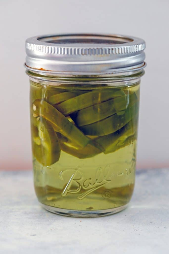 Head-on view of a mason jar filled with jalapeño slices infusing in vodka
