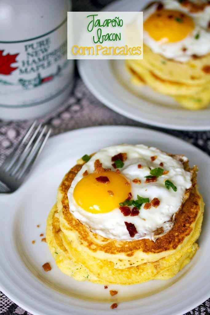 """A view from above of a stack of Jalapeño Bacon Corn Pancakes with an egg on top and a bottle of maple syrup in the background with """"Jalapeño Bacon Corn Pancakes"""" text on top"""