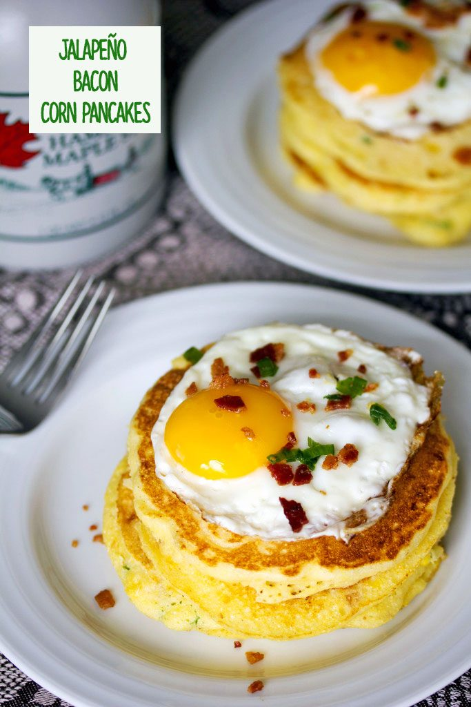 A view from above of a stack of jalapeño bacon corn pancakes with a sunnyside up egg on top on a white plate with a bottle of maple syrup in the background and recipe title at top