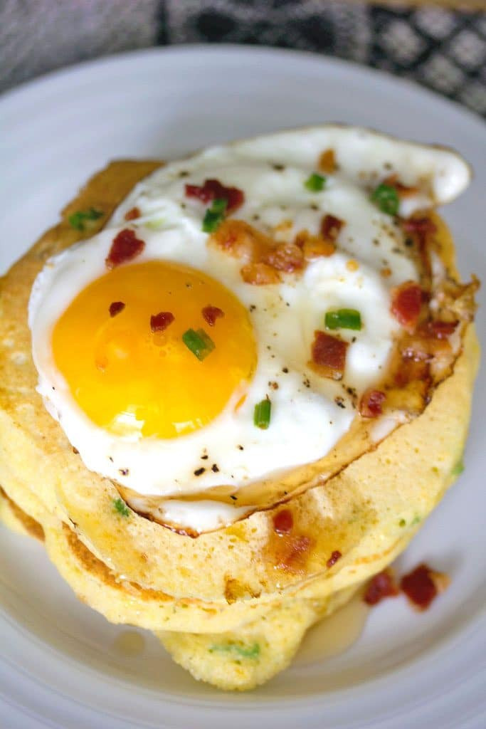 An up-close view of a stack of jalapeño bacon corn pancakes with a sunnyside up egg on top and crumbled bacon and chives
