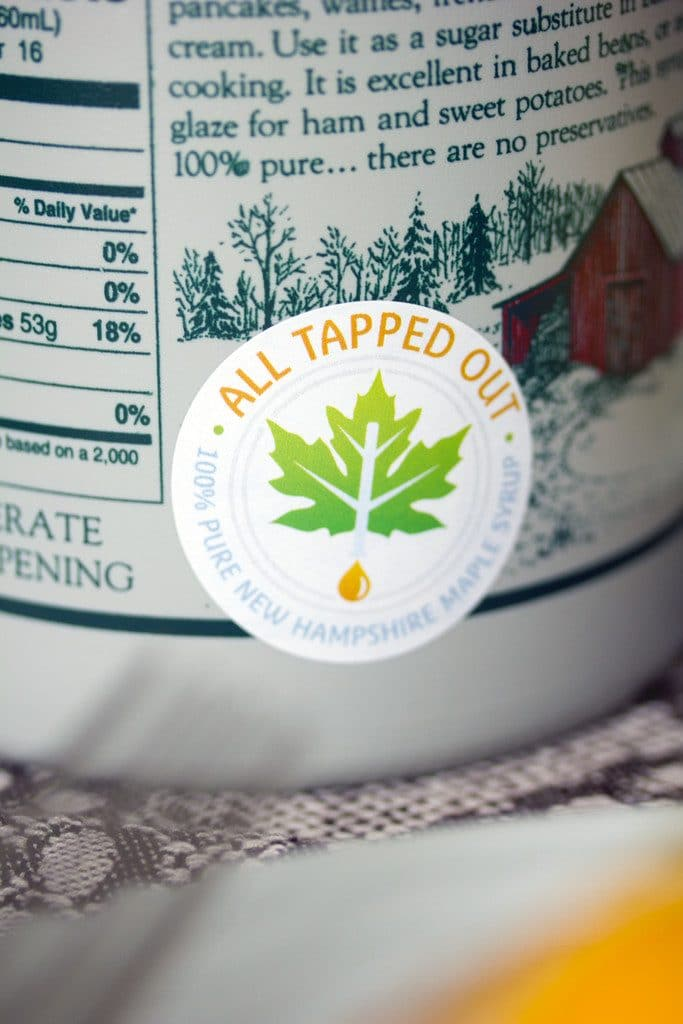 "An up-close view of a bottle of maple syrup with ""All Tapped Out"" sticker"