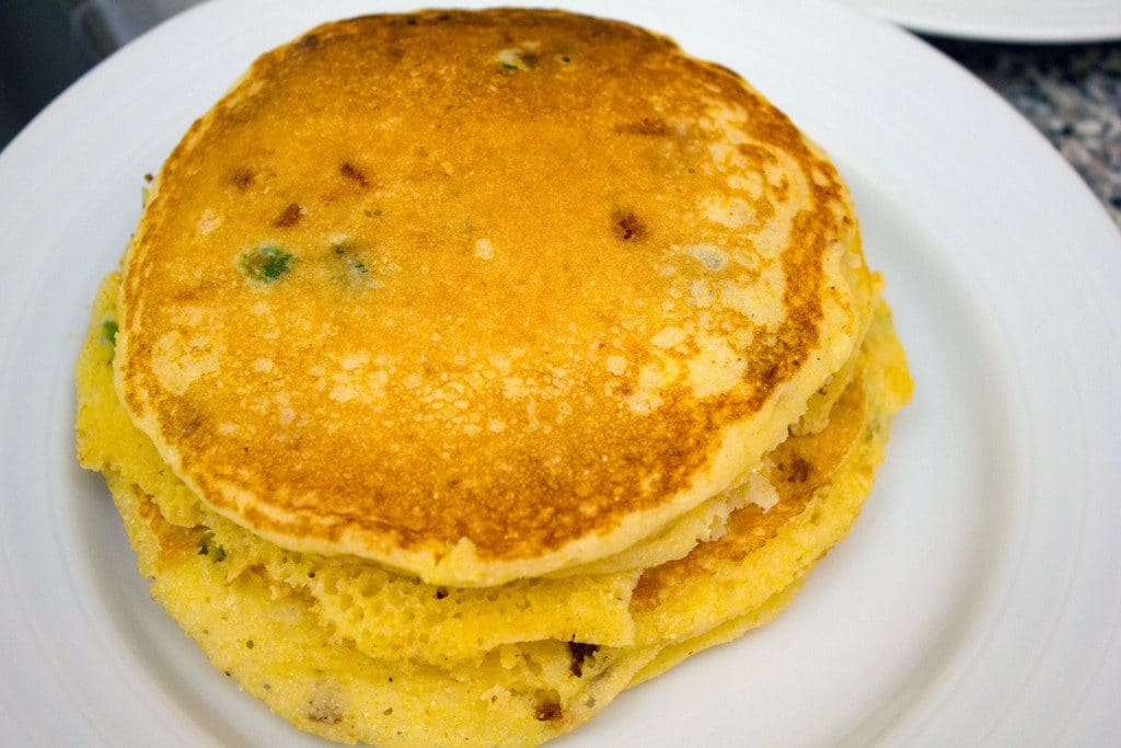 A stack of golden jalapeño bacon corn pancakes on a white plate