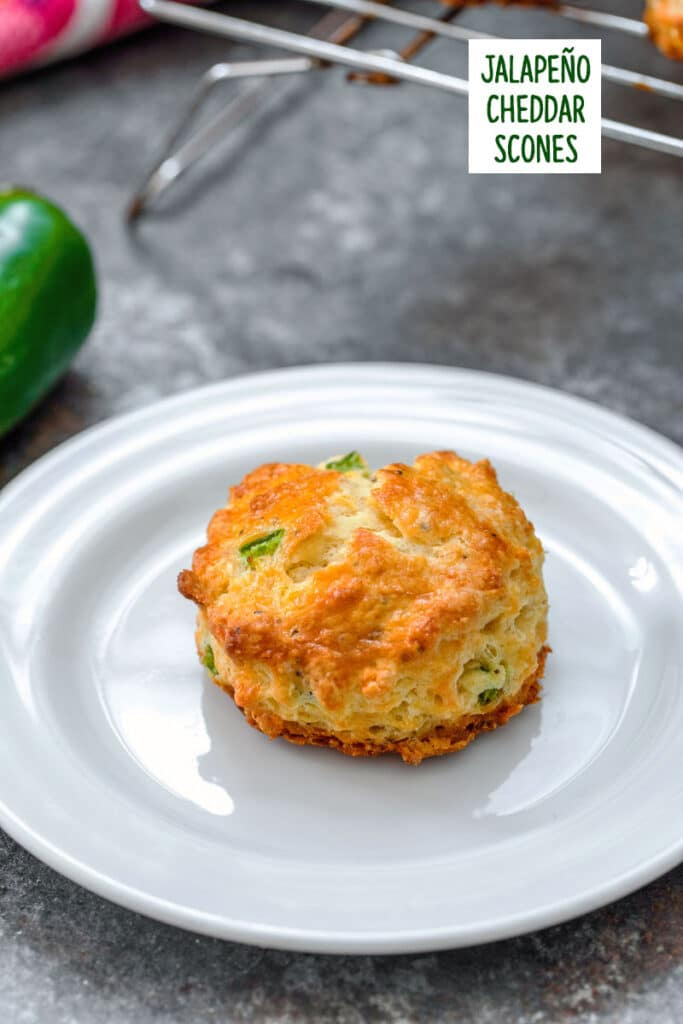 Close-up of a jalapeño cheddar scone on a white plate with recipe title at top of image