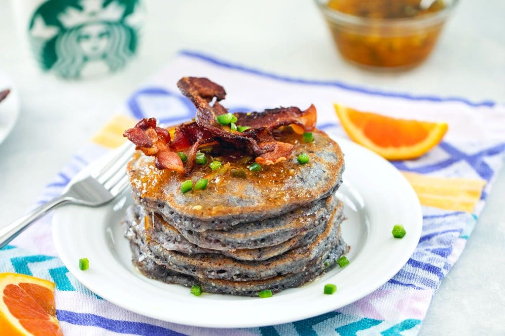 Head on view of stack of blue jalapeño cornmeal pancakes topped with crispy bacon on a white plate and purple and yellow napkin with orange slices and Starbucks mug in the background