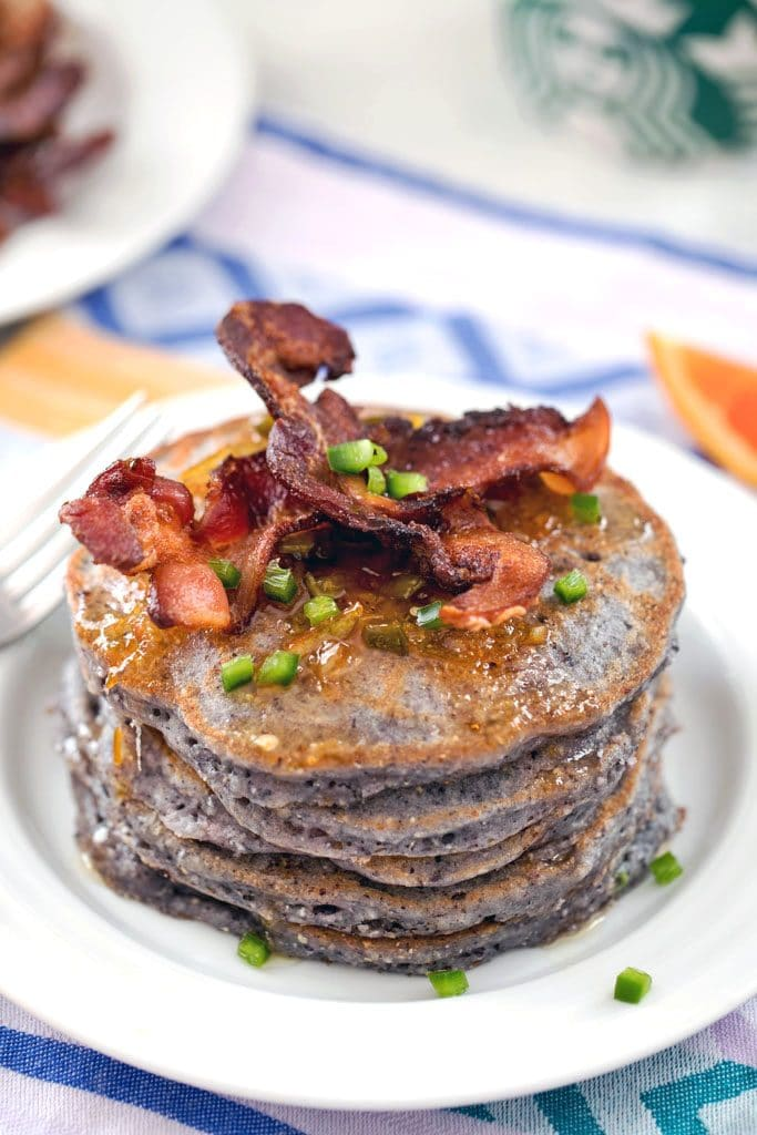 Hero image of blue jalapeño cornmeal pancakes in a large stack, topped with crispy bacon strips, orange syrup, and chopped jalapeño on a white plate