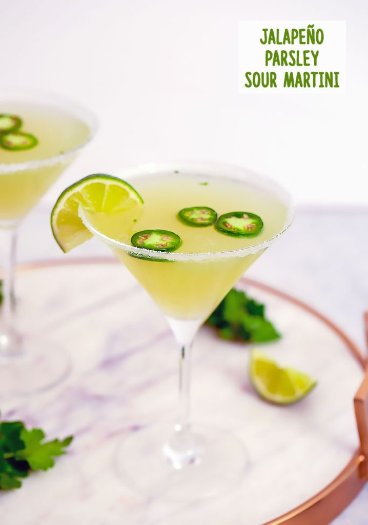 Head-on closeup view of jalapeño martini with vodka, parsley, lemon, and lime juice on a marble tray with lime wedge and parsley in background and recipe title at top