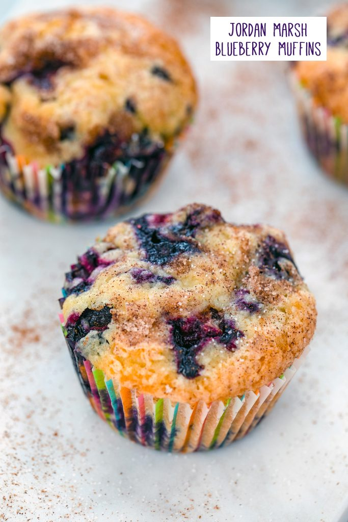 Overhead view of several Jordan Marsh blueberry muffins with recipe title at top