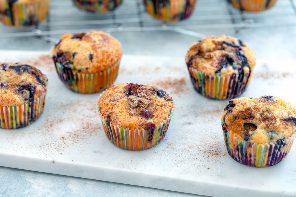 Landscape view of several Jordan Marsh blueberry muffins on a marble board with baking rack with more muffins in the background