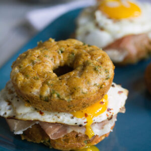 Kale Cheddar Doughnut Egg Sandwiches -- Eggs and prosciutto sandwiched between two savory doughnuts | wearenotmartha.com
