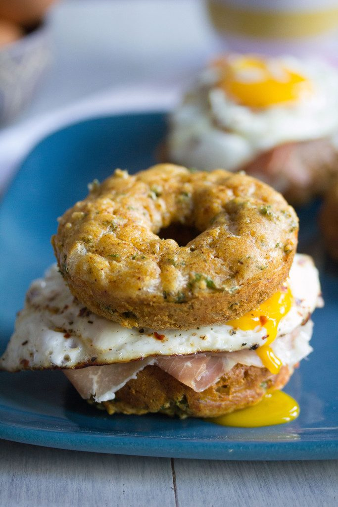 Kale Cheddar Doughnut Egg Sandwiches -- Eggs and prosciutto sandwiched between two savory doughnuts | wearenotmartha.com