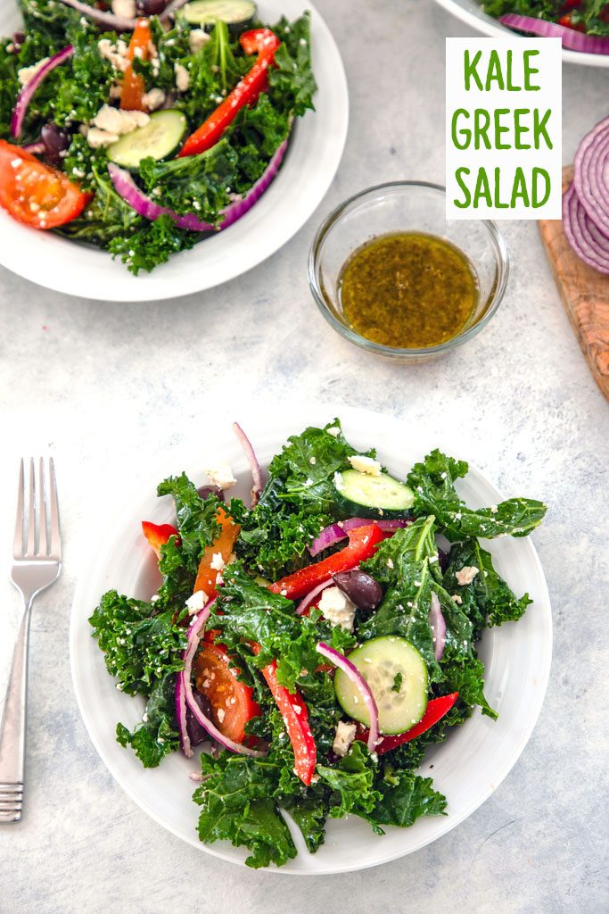 Overhead view of kale Greek salad in a serving bowl with fork, bowl of dressing, and second salad bowl in the background and recipe title at top