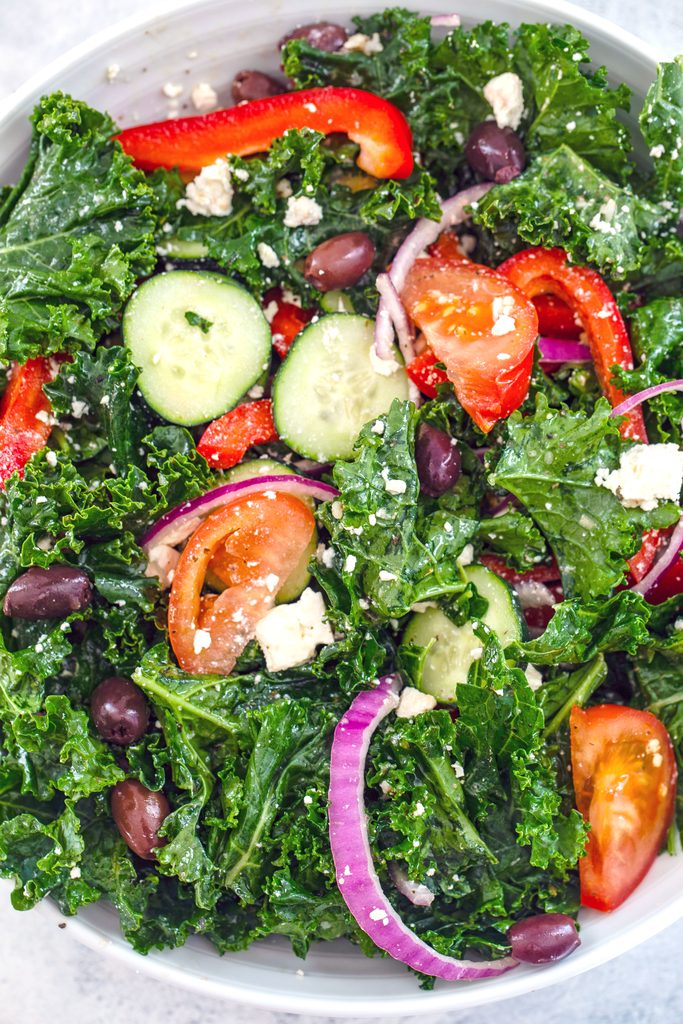 Overhead view of ingredients for kale Greek salad all mixed together in serving bowl