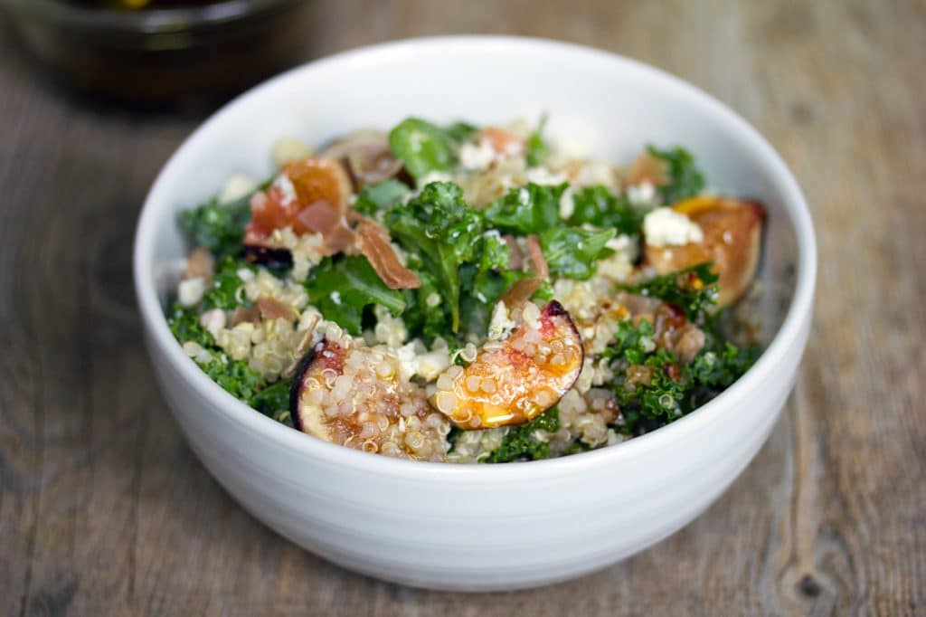 Landscape view of lemony kale, quinoa, and fig salad in a white bowl n a wooden surface