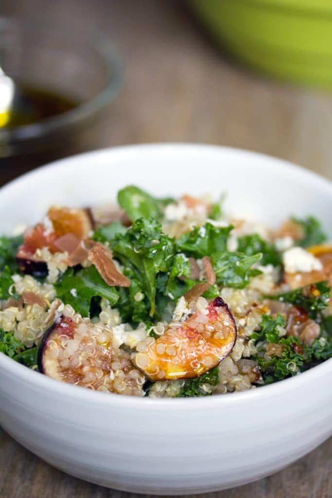 Head-on closeup view of lemony kale, quinoa, and fig salad in a white bowl