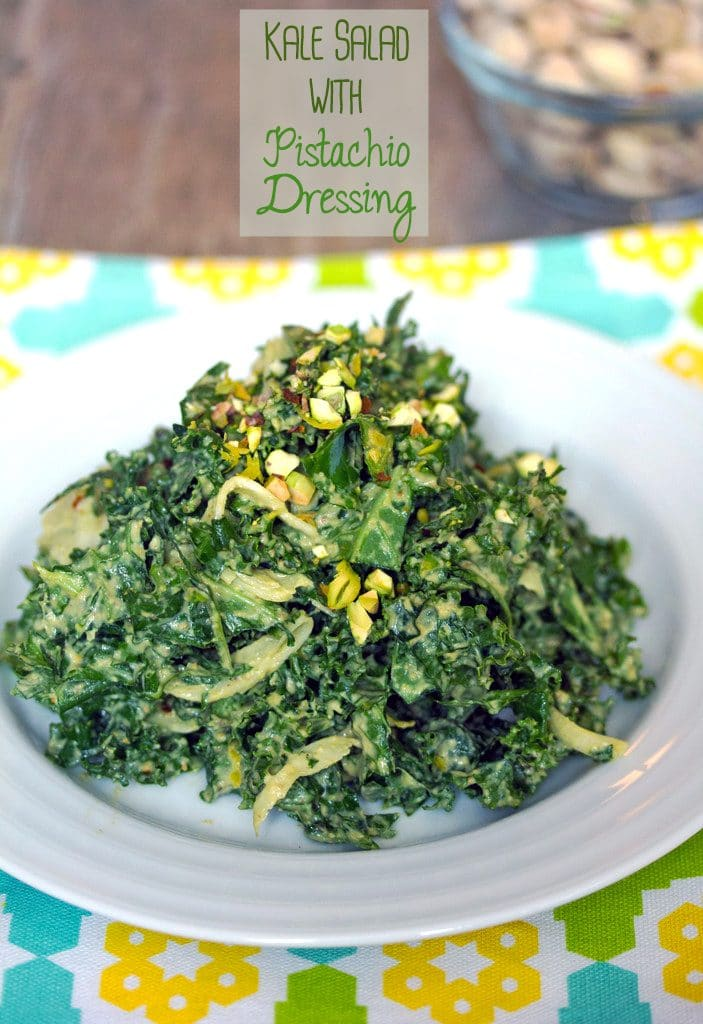 "Head-on view of chopped kale salad with pistachio dressing piled high on a white plate with a bowl of pistachios in the background and ""Kale Salad with Pistachio Dressing"" text at the top"