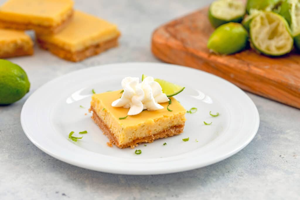 Head-on landscape view of key lime bar on a white plate with juiced key limes, whole key lime, and more bars in background