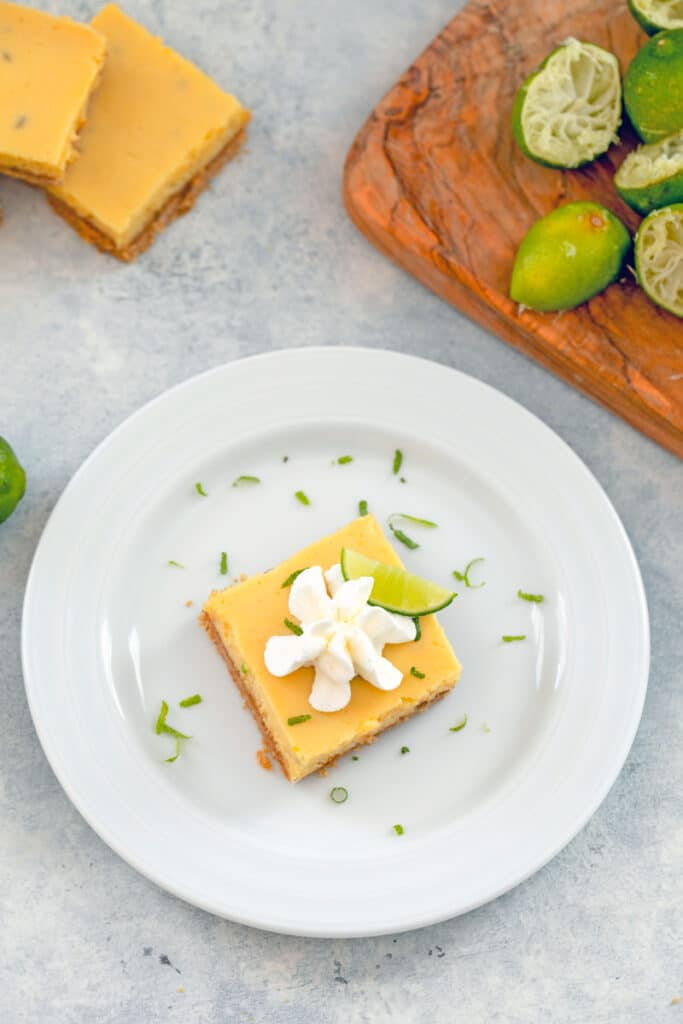 Overhead view of a key lime bar with whipped cream on a white plate with lime zest with juiced key limes and more bars in the background