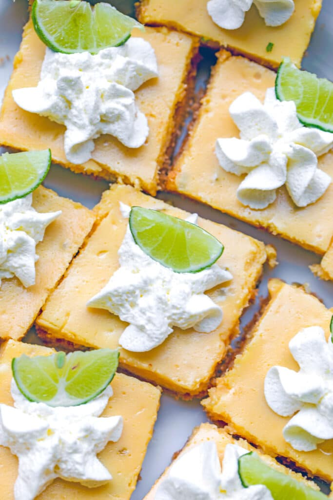 Overhead close-up view of multiple key lime  bars with whipped cream and key lime wedges