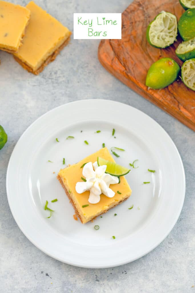 Overhead view of a key lime bar with whipped cream on a white plate with lime zest with juiced key limes and more bars in the background and recipe title at top