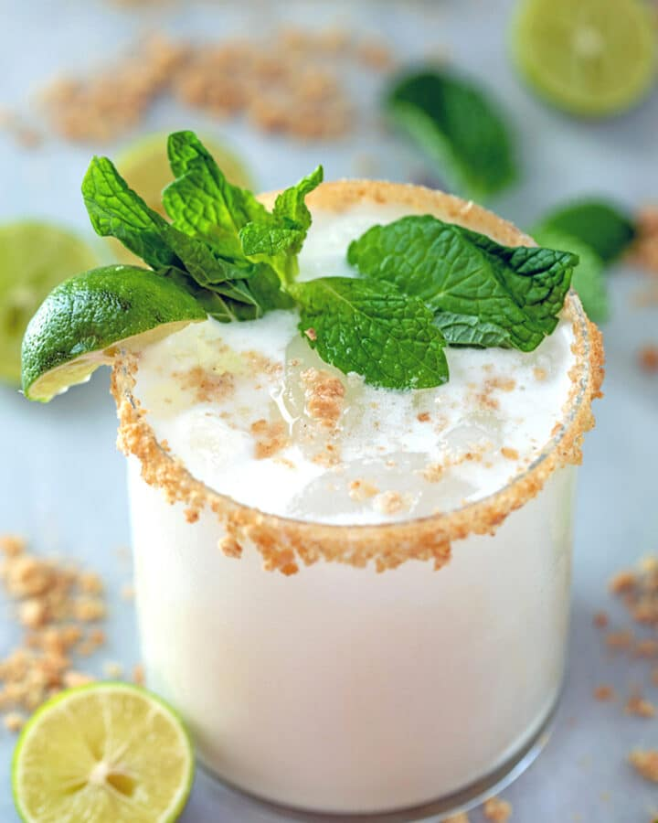 Key Lime Pie Mojito -- This summer cocktail is key lime pie in a glass, complete with fresh mint, a graham cracker rim, and a splash of cream. The only thing missing is the sunny day necessary to enjoy this Key Lime Pie Mojito! | wearenotmartha.com