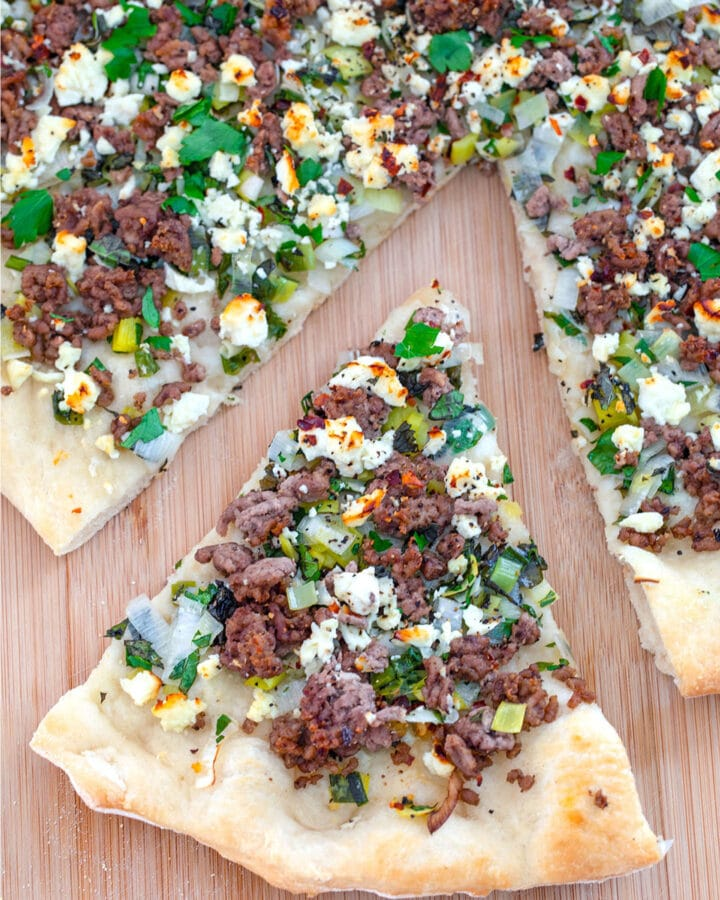 Overhead view of a slice of Lamb Flatbread with Mint and Feta pulled out from the rest of the pizza on a wood board