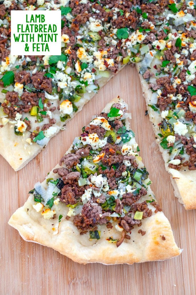 Overhead view of a slice of Lamb Flatbread with Mint and Feta pulled out from the rest of the pizza on a wood board with recipe title at top